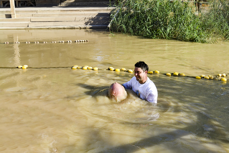 a man toes underwater at his baptism in the Jordan River. The priest holds his hands