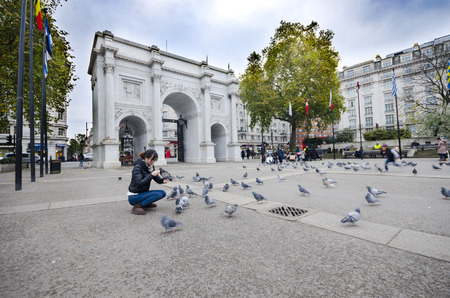 Woman feeding peageons in front of Marble Arch monument in London, UK