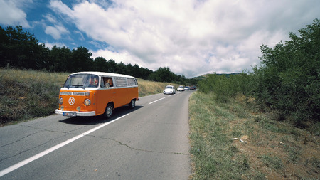 Kocani, Macedonia - 24 Jun, 2018: VW old cars and vans on exhibition of vintage cars driving down the rural mountain road Stock Photo