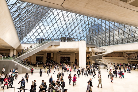 Paris, France - 05 May, 2017: People at the main entrance of Louvre museum, under the famous glass Pyramid. Paris, France