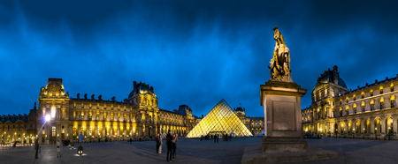Panorama of Louvre museum with glass pyramid and monuments at twilight Stock Photo