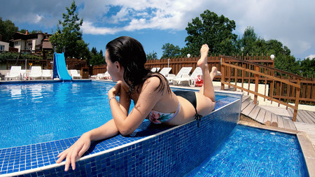 Beautiful brunette teen girl lying by the pool relaxing during summer vacation