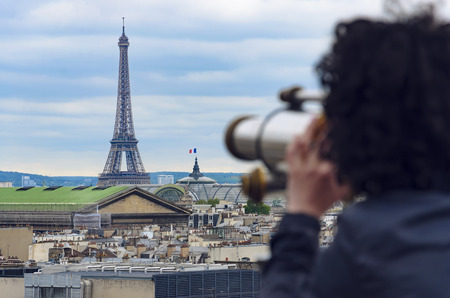 Woman looking through coin operated binocular at Eiffel Tower in Paris, France