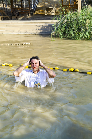 Organized baptism for group of pilgrims in river of Jordan, the place which is believed that Jesus was baptized