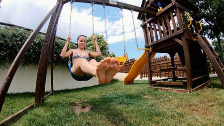 Teen Girl in Bikini Swings On A Swing Set Under A Summer Sky