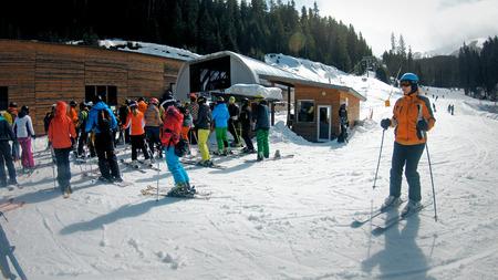 Bansko, Bulgaria - circa Feb, 2018: Snowboarders on turnstiles at ski pass automatic entrance for ski lift at Bansko resort, Bulgaria, slow motion