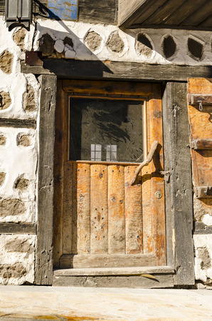 Old door marking the entrance to an old building with stone walls decoration, Bansko, Bulgaria Фото со стока
