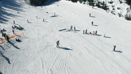 POV from ski lift with aerial view of skiers on slope and distant snow covered mountain peaks