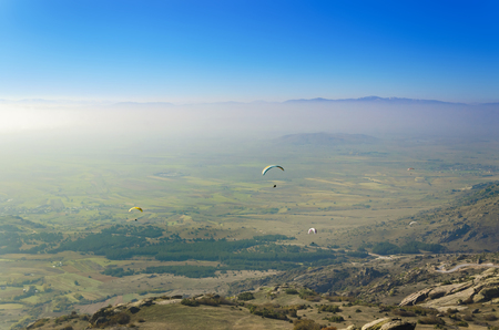 A lot of paragliders above misty foggy valley Stock Photo