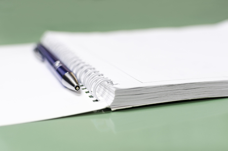 Ein Stift neben einem Notizbuch mit spiralförmigem, selektivem Fokus auf die Stiftkugelspitze Standard-Bild
