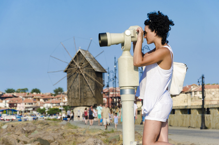 Woman looking in coin observation binoculars in old town of Nesebar in Bulgaria