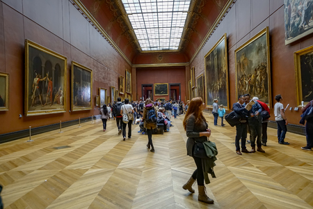 Paris, France - circa May, 2017: Many people appreciate paintings in the Louvre Museum in Paris, France. The Louvre is the worlds largest museum and a historic monument in Paris, France