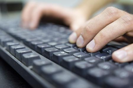 Bediener, der auf schmutziger Tastatur tippt.