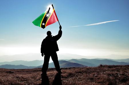 Erfolgreicher Silhouette-Mann-Gewinner schwenkt die Flagge von St. Kitts und Nevis auf dem Gipfel