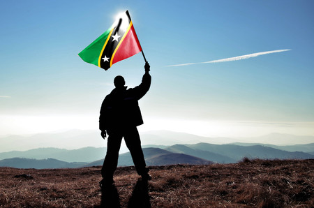 Gagnant réussi de l'homme silhouette agitant le drapeau de Saint-Kitts-et-Nevis au sommet du sommet de la montagne