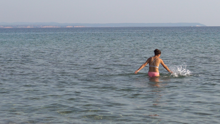 Lonely young woman plays alone in sea shallow water splashing with her hands