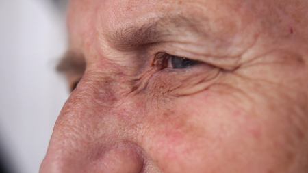 age, vision and old people concept - close up of senior woman face and eye Stock Photo