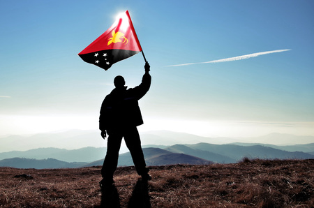Successful silhouette man winner waving Papua New Guinea flag on top of the mountain peak