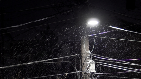 Dense snowflakes on dark night under the street led light with electric cable wires instalation