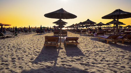 Beach chairs with umbrella on the beach at sunset. Cinematic steadicam shot