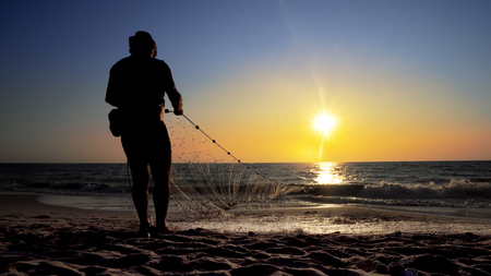 Fishermen fishing in the early morning golden light manual hand pulling the net Stock Photo