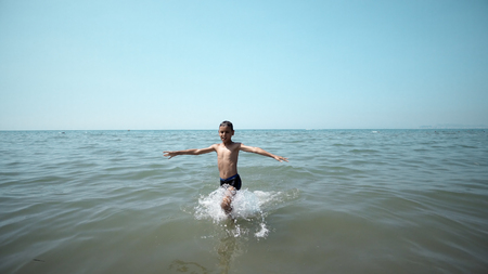 Happy boy getting out from the sea water. Front cinematic steadicam view 版權商用圖片
