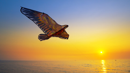 Close up colored toy kite flying high in air against gold sunset sky background sun on sea beach Stock Photo