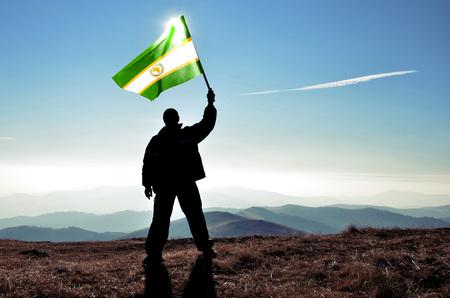 Successful silhouette man winner waving Organization of African Unityflag on top of the mountain peak
