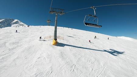 Ski lift draging through a pine forest area at sunrise to the mountain ski slopes winter resort, POV shot Stock fotó