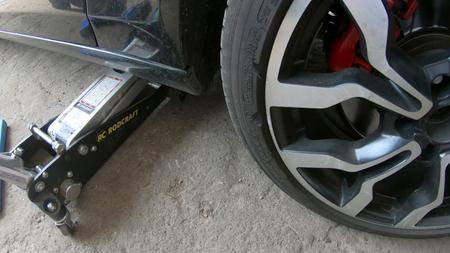Kocani, Macedonia - 24 de junio de 2018: Sección baja del mecánico masculino reparando el neumático del coche en el taller de reparación Editorial
