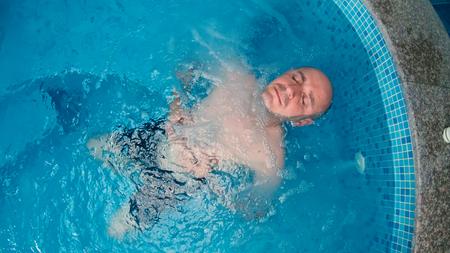 Glatzköpfiger Mann genießt im Thermal Spa badewanne