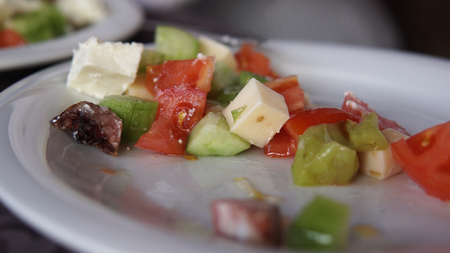 Eating vegetable salad, observing diet and counting calories, wellness.tomato, cheese, ham, mushrooms, cinematic dof close up