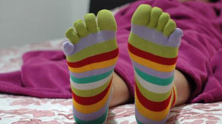 Vrouwelijke benen in sokken met tenen ontspannen in bed Stockfoto