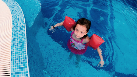 Girl with inflatable arm bands play in outdoor pool