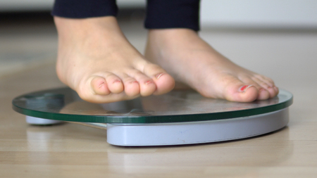 Girl feet on scales to measure the weight of the empty wooden floor