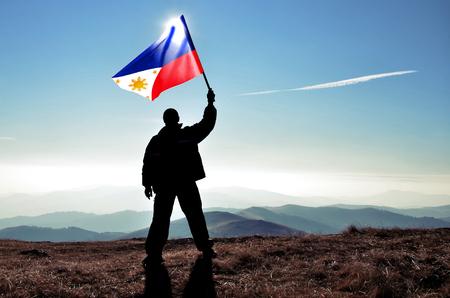 Successful silhouette man winner waving Philippines flag on top of the mountain peak Фото со стока