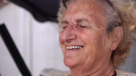 Old woman smiling and talking during the day relaxing on porch swing bed Фото со стока - 120404428