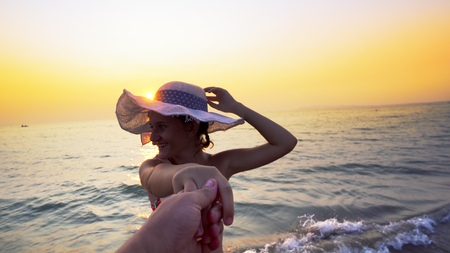 Romantic couple on honeymoon at sunset. Smiling girlfriend with hat walking with holding hand of her boyfriend on the beach. Couple enjoying summer vacation on beach Фото со стока