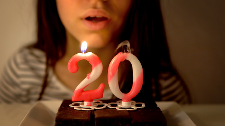 Girl blowing out a 20th birthday candle on a cupcake Фото со стока - 120405566
