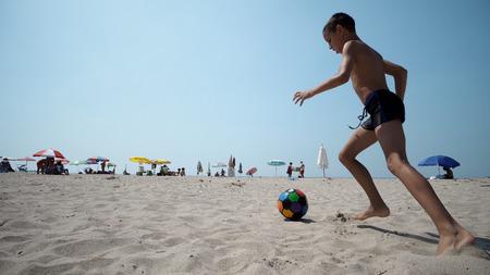 Cheerful kid playing football, running barefoot on wet sandy beach, kicking ball in slow motion, cinematic shot Фото со стока - 120405905