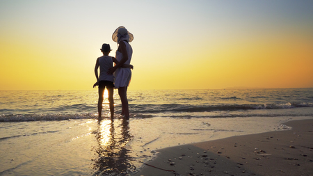 Mother with white dress and hat and son with hat standing barefoot on beach looking at the setting sun splashed by sea waves. Travel concept