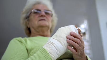 Old woman massage her injured broken hand sitting, cinematic dof Фото со стока - 120407508