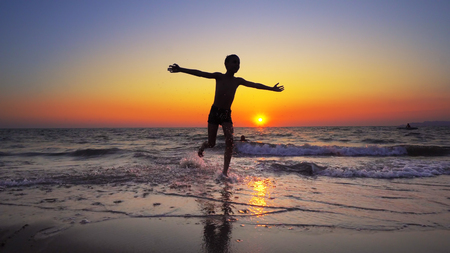 Boy child is running out of water on a sea beach at sunset, cinematic steadicam shot Фото со стока - 120407509