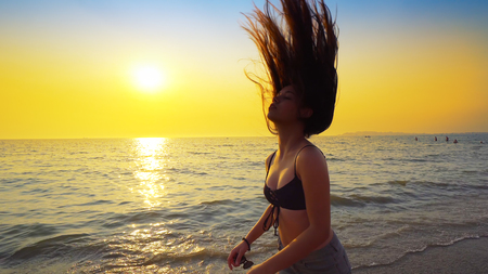 Beautiful model in swimsuit posing on the beach in sunset sunlight with long hair making forms Фото со стока - 120408863