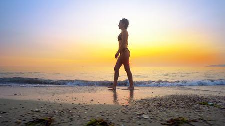 Fit woman walk on beach at sunset splashing water on sea waves Фото со стока - 120411958