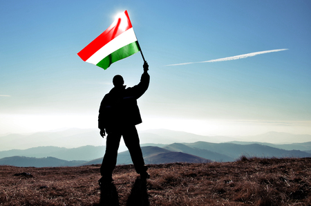 Successful silhouette man winner waving Hungary flag on top of the mountain peak