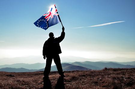 Successful silhouette man winner waving Cook Islands flag on top of the mountain peak Фото со стока - 120412093
