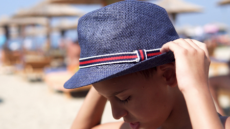 Happy hispanic boy with hat smiling on beach and give a kiss to camera Фото со стока