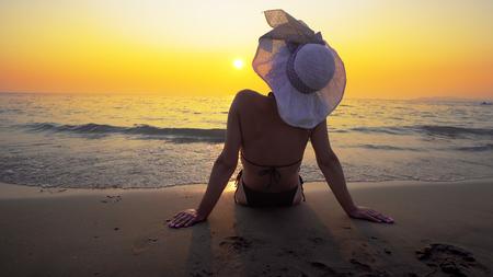 Hispanic woman with hat sitting on beach at sunset. Sea waves splash her body. Travel concept Фото со стока - 120419604