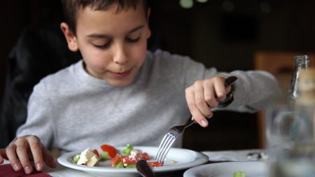 Boy eating fresh green salad in an outdoor cafee. Healthy lifestyle Фото со стока - 120427336